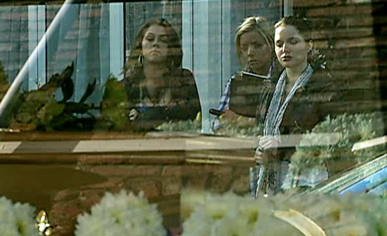 Sophie, Sian and Rosie looking at hearse in Street - blanche