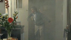 Roy fanning door in smoke-filled apartment