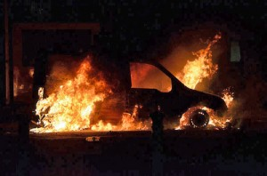 Burning_car_Manchester_riots-(by-Richard-Hopkins)