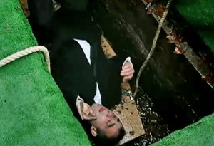 Kevin lying on coffin in grave
