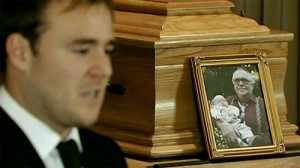 Tyrone giving eulogy, Jack's photo beside him