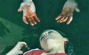 Tracy on ground and bloody hands over her
