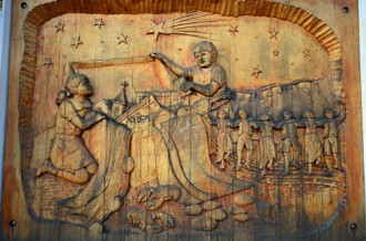 carved panel telling Acadian history on side of Museum building, Miscouche