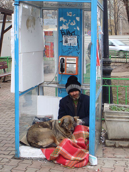 homeless man and dog in phone booth RO_B_new_Bucharest_apartment-photo-Miehs-wikicommons