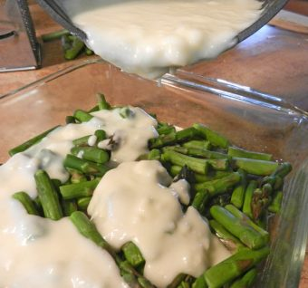 pouring sauce over asparagus